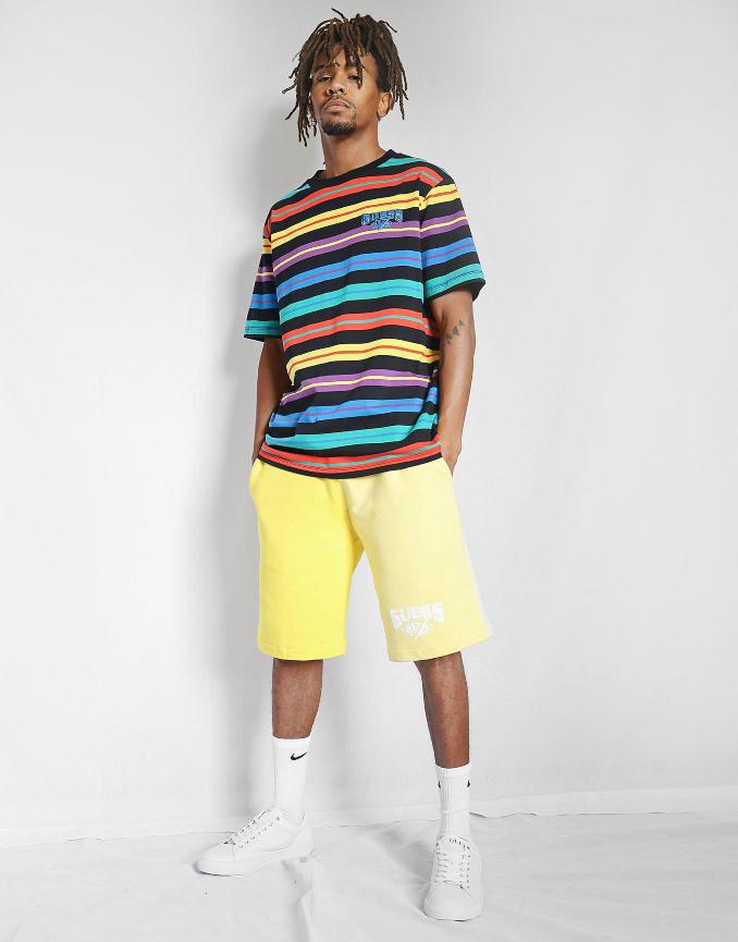 Ropa de J Balvin con Guess, camiseta a rayas negra y pantalón corto amarillo